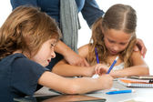 Teacher supervising kids homework. — Stock Photo