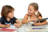 Dvě děti diskusi domácí úkol na stůl. — Stock fotografie