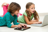 Two kids on floor with laptop and tablet. — Stock Photo