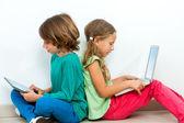 Dwoje dzieci towarzyskich z laptopa i tabletki. — Zdjęcie stockowe