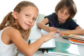 Young kids doing schoolwork together at desk. — Stok fotoğraf