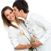 Boy giving girl a rose and romantic kiss. — Stock Photo