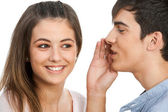 Boy whispering in cute girls ear. — Stock Photo