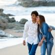 Cute teen couple walking along beach. — Stock Photo