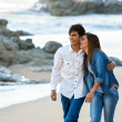 Cute teen couple walking along beach. - Stock Photo