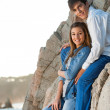 Young couple sitting on rocks at seaside. — Stock Photo