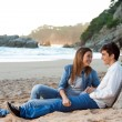 Young handsome couple sitting on beach. — Stock Photo