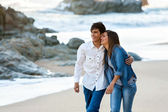 Cute teen couple walking along beach. — Stock Photo