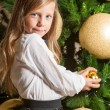 Cute girl at home with christmas tree. — Stock Photo