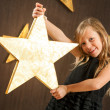 Cute girl holding big golden star. — Stock Photo #17135291