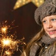 Cute girl looking at festive fire sparks. — Stock Photo #17135305