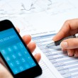Female hands calculating budget with smart phone. - Stock Photo
