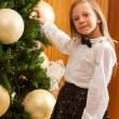 Little girl decorating christmas tree. - Stock Photo
