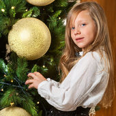 Cute girl decorating christmas tree. — Stock Photo
