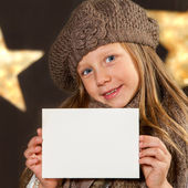 Cute girl with beanie holding white card. — Stok fotoğraf