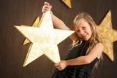 Sevimli kız büyük bir altın yıldız holding. — Stok fotoğraf