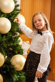 Little girl decorating christmas tree. — Stock Photo