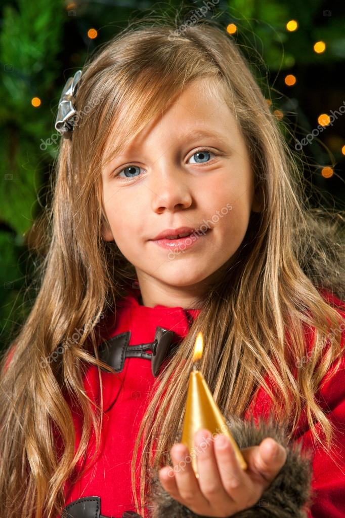 Cute blond girl holding golden candle at christmas tree. — Stock Photo #17135229