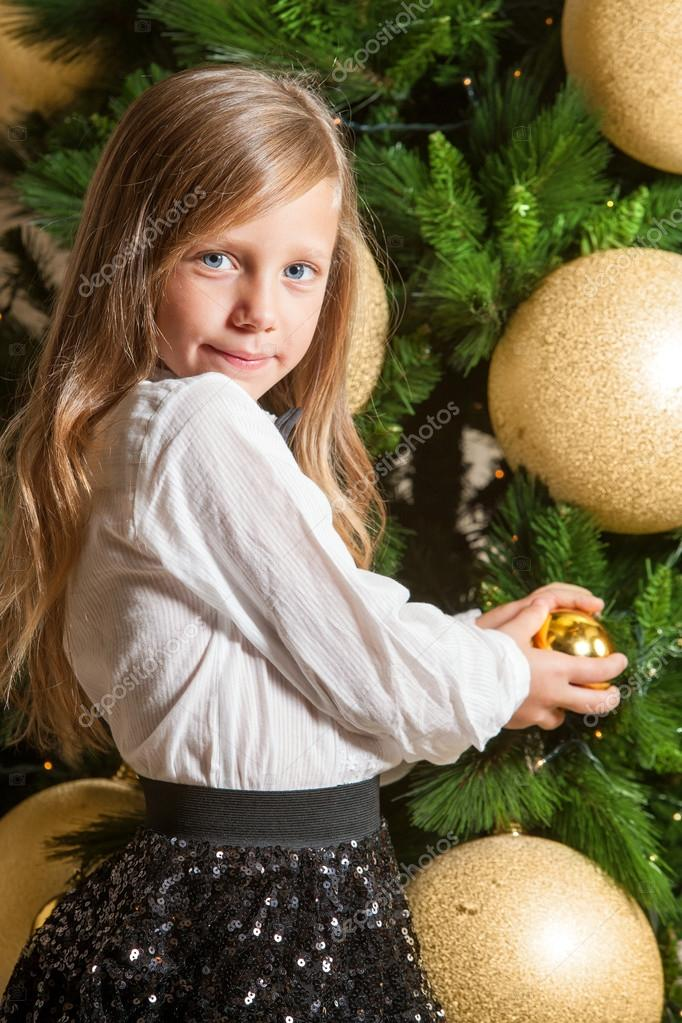 Portrait of cute little girl at home in front of christmas tree. — Stock Photo #17135241