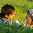 Stock Photo: Couple laying in grass field at sunset.