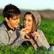Girl showing flower to boyfriend outdoors. - Stok fotoğraf