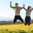 Teen couple jumping outdoors. — Stock Photo #17693261