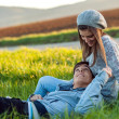 Young couple relaxing in green grass field. — Stock Photo