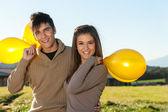Linda pareja adolescente al aire libre con globos. — Foto de Stock