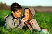 Girl showing flower to boyfriend outdoors. — Stock Photo