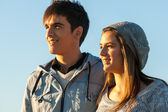 Handsome teen couple looking in the distance. — Stock Photo