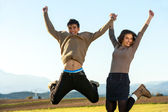 Young couple hanving fun jumping. — Stock Photo