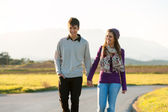 Young couple wandering in sunny countryside. — Stock Photo