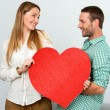 Cute couple holding big red heart sign. — Stock Photo