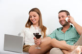 Couple relaxing with glass of wine on couch. — Stock Photo