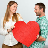 Cute couple holding big red heart sign. — Foto de Stock