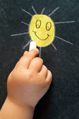 Infant hand drawing a smiling sun. — Stock Photo