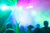 Disco laser lihgts illuminating crowd. — Stock Photo