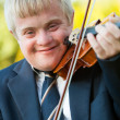 Close up portrait of handicapped boy with violin. - Stock Photo