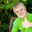 Cute handicapped boy showing thumbs up outdoors. - Foto de Stock