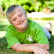 Portrait of handicapped boy on green grass. - Foto de Stock
