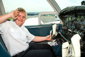 Young handicapped pilot saluting in cabin. — Stock Photo