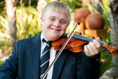 Smiling handicapped boy playing his violin. — Stock Photo