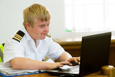 Young handicapped pilot working with laptop. — Stock Photo