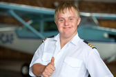 Young pilot with down syndrome showing thumbs up. — Stock Photo