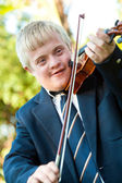 Cute handicapped boy playing violin. — Stock Photo