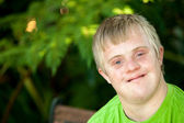 Portrait of cute handicapped boy in garden. — Stock Photo