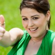 Cute girl showing thumbs up in green field. - Stockfoto