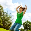 Stock Photo: Euphoric girl jumping in park.