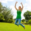 Young girl jumping high in green park. — Stock Photo