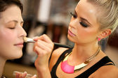 Attractive female make up artist at work. — Stock fotografie